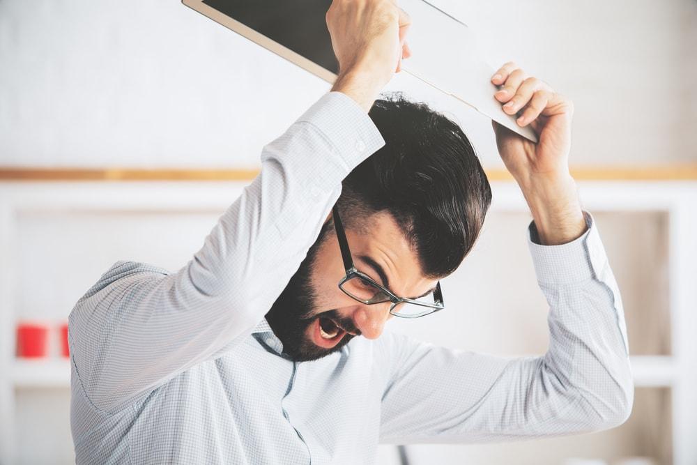 Ein junger Mann mit Brille hält ein Notebook in der Hand und will es hinunter werfen