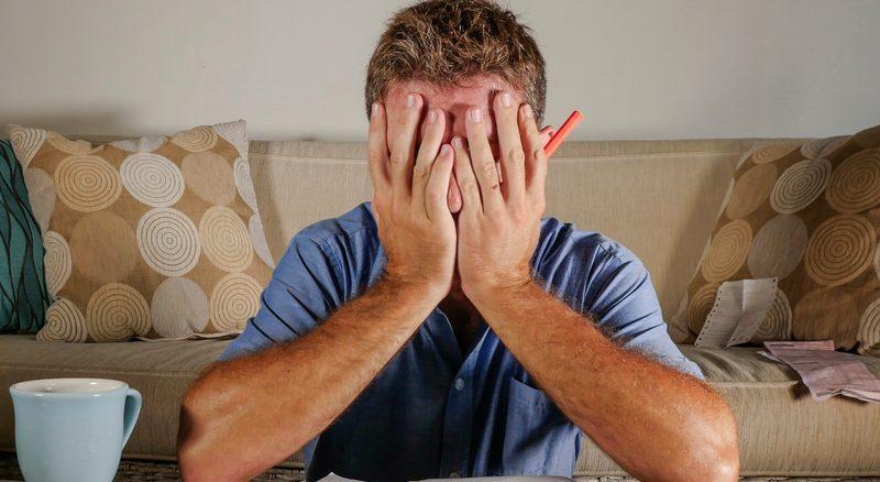 Ein junger Mann sitzt verzweifelt vor einem Heft und hält sich die Hände vor das Gesicht