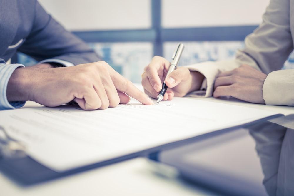 Ein Vertrag liegt auf dem Tisch und wird unterschrieben