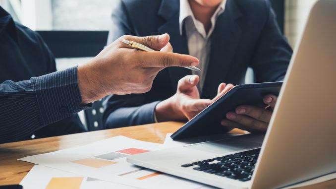 Zwei Geschäftsmänner sitzen vor einem Notebook, eine Person hält ein Tablet in der Hand