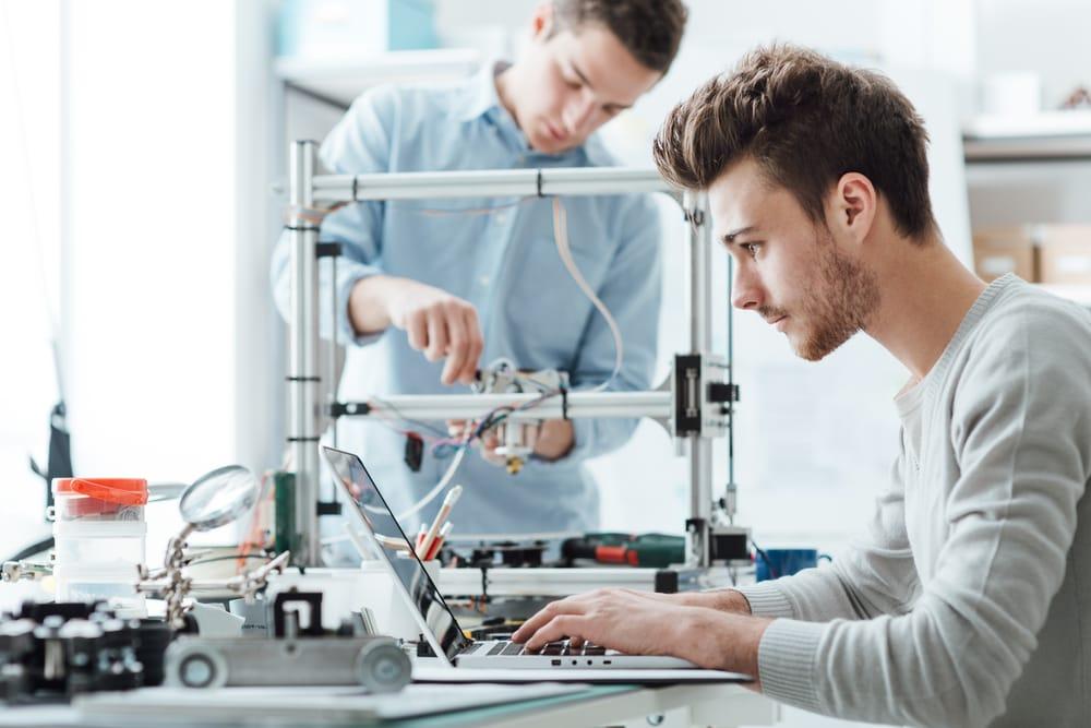Junger Informatik-Student sitzt in Labor am Laptop; im Hintergrund Basteleien