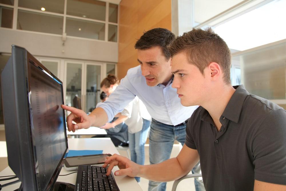 Ein Fachinformatiker in der Ausbildung an einem PC mit dem Lehrer neben sich
