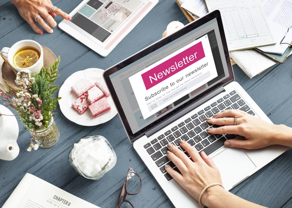 Hand tippt auf Laptop und gestaltet einen Newsletter