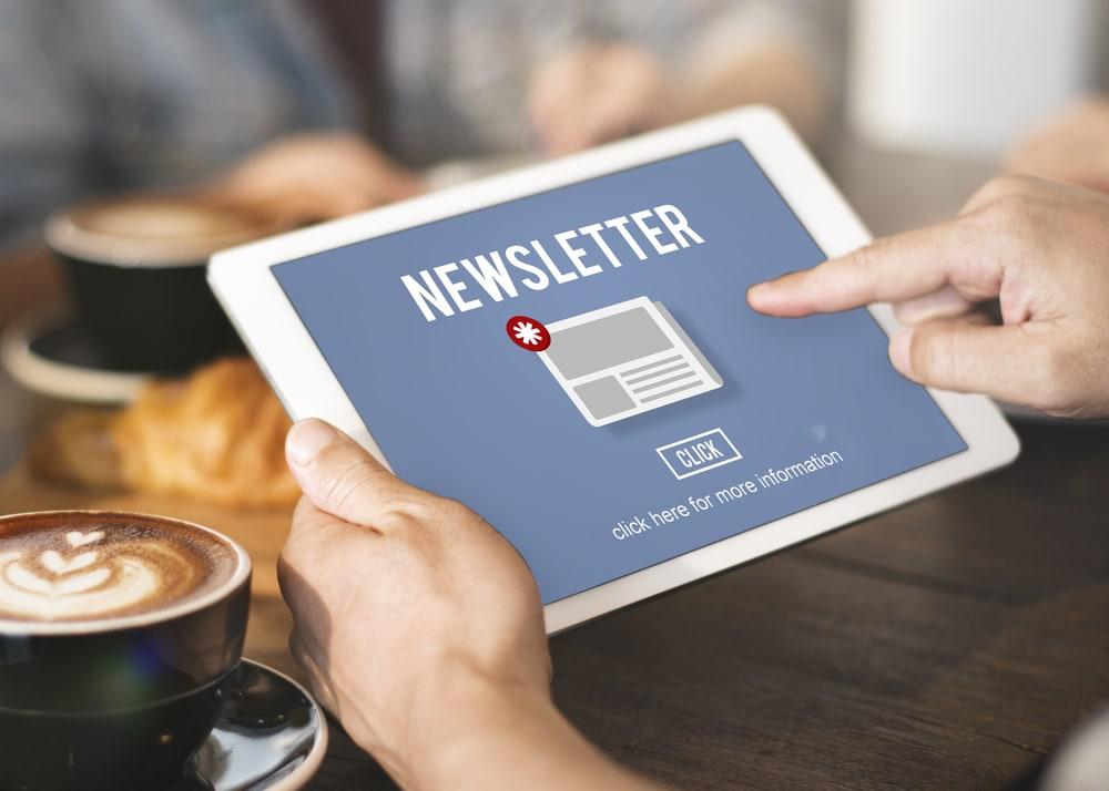 Hand tippt auf Tablet, um Newsletter zu öffnen