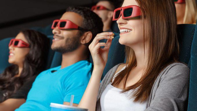 Ein junges Mädchen sitzt im Kino, isst Popcorn und trägt eine 3D Brille