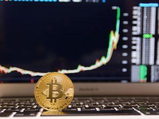 Bitcoin mit Kursentwicklung im Hintergrund