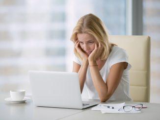 Frau hilflos vor dem Notebook