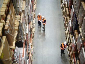 Arbeitnehmer stehen vor einem Hochregal zwecks Inventur.