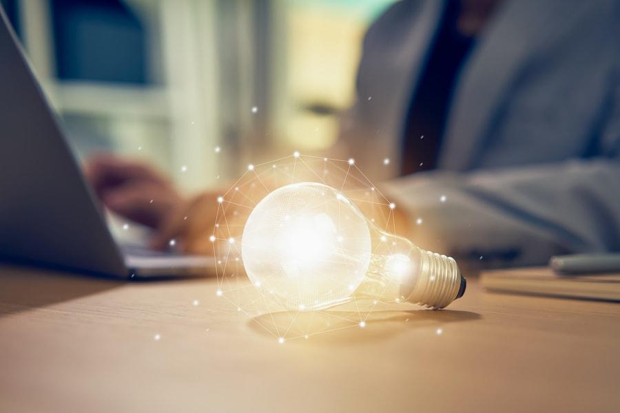 Eine helle Glühbirne liegt auf dem Tisch, im Hintergrund arbeitet jemand am Notebook