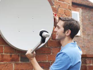 Mann montiert Satellitenschüssel