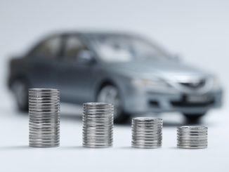 Münzen gestapelt vor einem Auto
