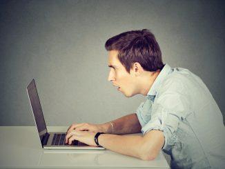 Junger Mann sitzt erstaunt vor dem Notebook