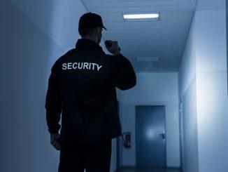Security-Mann steht im Flur eines Gebäudes