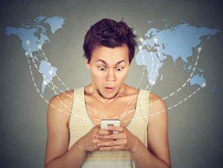 Junger Mann mit Mobiltelefon in der Hand