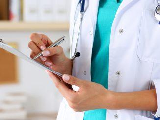 Eine Ärztin schreibt etwas auf