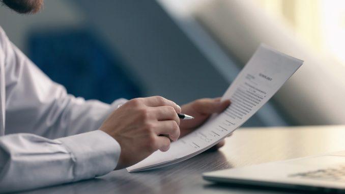 Ein Geschäftsmann hält einen Vertrag in der Hand