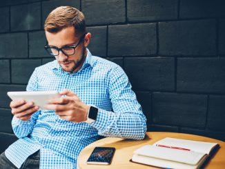 Ein junger Mann spielt Browsergames auf dem Tablet