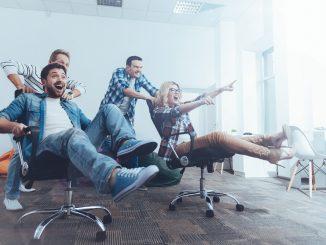 Angestellte sitzen fröhlich auf Bürostühlen im Büro