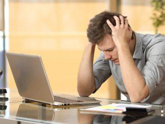 Ein junger Mann sitzt verzweifelt vor dem Notebook