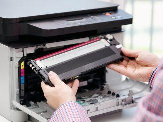 Ein Angestellter legt eine Tonerkartusche in den Drucker ein