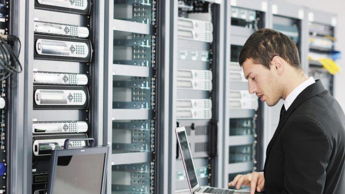 EIn Techniker steht vor einem Serverschrank