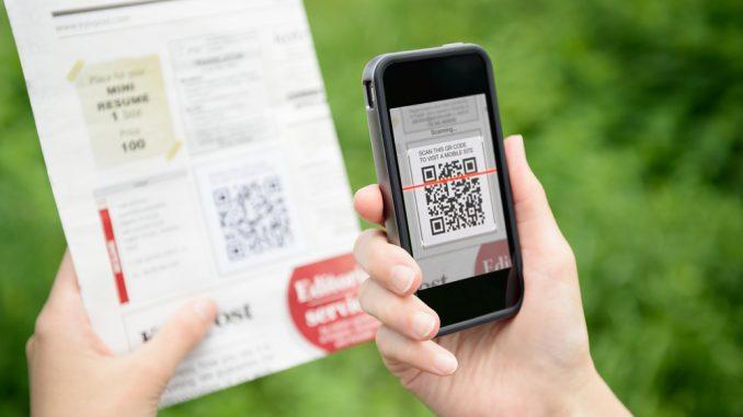 Jemand scannt einen QR-Code mit dem Smartphone