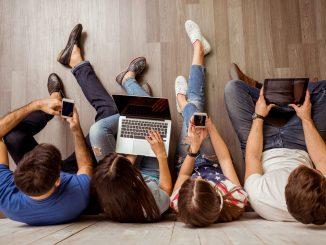 Vier junge Menschen mit Laptops und Smartphones