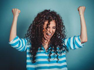 Eine Frau reißt die Hände hoch und jubelt