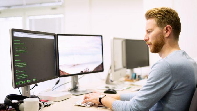 Fachinformatiker sitzt am Arbeitsplatz vor drei Monitoren