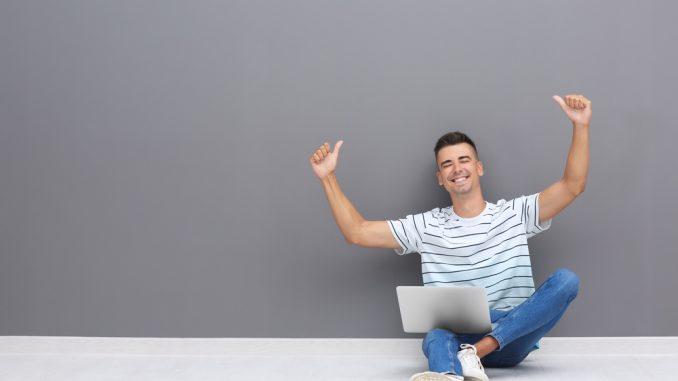 Ein junger Mann sitzt mit dem Notebook auf dem Boden und schreibt eine Kurzbewerbung