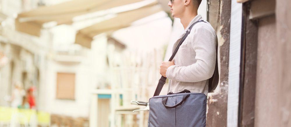 Ein junger Mann trägt eine Laptoptasche um die Schulter