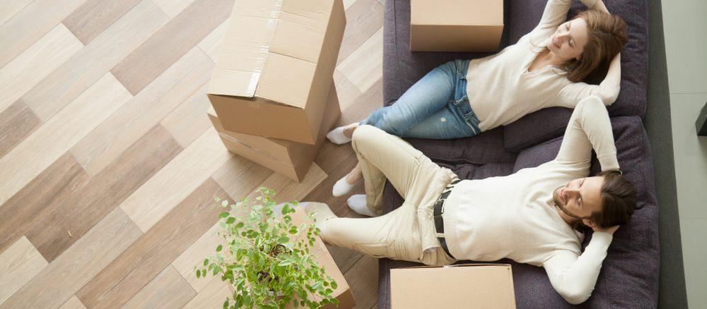 Ein Paar sitzt auf dem Sofa vor gepackten Kartons
