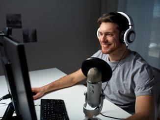 Ein junger Mann sitzt an seinem PC, hat ein Headset auf und spricht in ein Standmikrofon