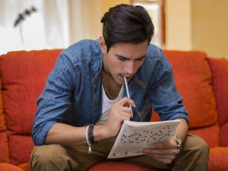 Ein junger Mann sitzt auf dem Sofa und macht ein Kreuzworträtsel