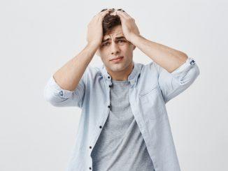 Ein junger Mann fasst sich verzweifelt an den Kopf