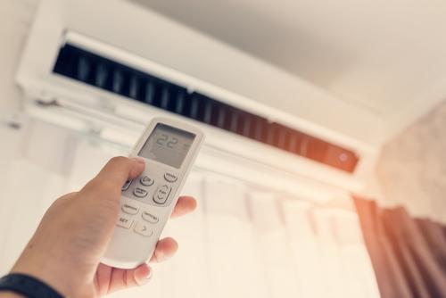 Jemand bedient eine Klimaanlage mit der Fernbedienung.