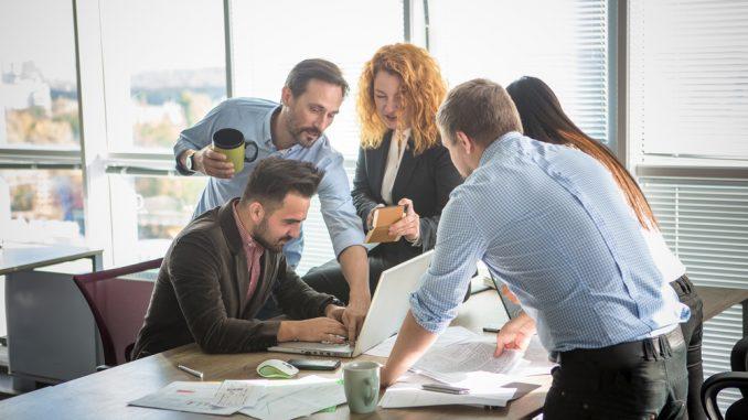 Mehrere Angestellte stehen zusammen am Tisch
