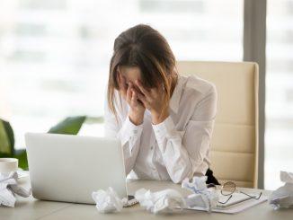 Eine junge Frau sitzt hilflos am Arbeitsplatz vor dem Notebook