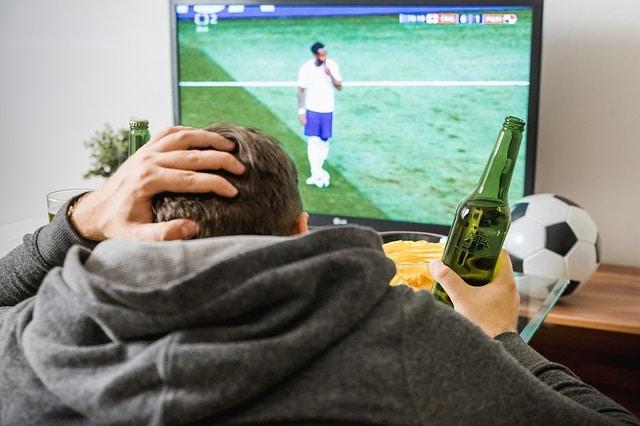 Ein junger Mann sitzt mit einer Bierflasche in der Hand vor dem Fernseher und schaut Fußball