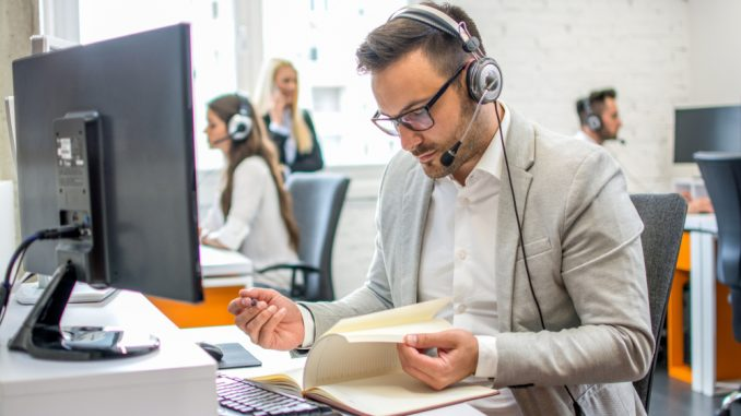 Ein junger Mann im Anzug sitzt mit Headset vor dem PC am Arbeitsplatz