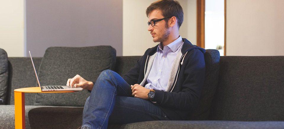 Ein junger Mann sitzt auf der Couch und bedient ein Notebook
