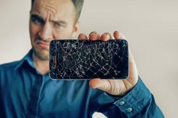 Ein junger Mann hält ein Smartphone mit Displayschaden in die Kamera