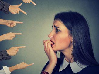 Ein junges Mädchen guckt ängstlich und auf ihr zeigen ganz viele Finger