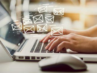 Zwei Hände auf dem Notebook mit ganz vielen E-Mail-Symbolen