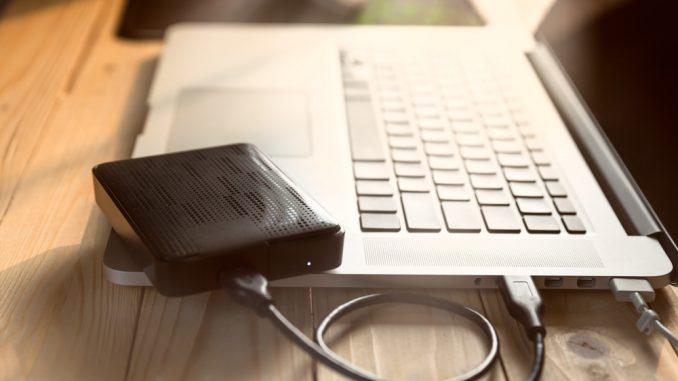 Eine externe Festplatte, die an einem Notebook angeschlossen ist.