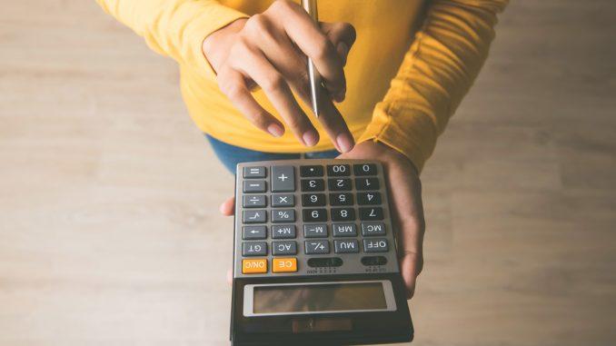 Eine Person im gelben Pullover hat einen Taschenrechner in der Hand