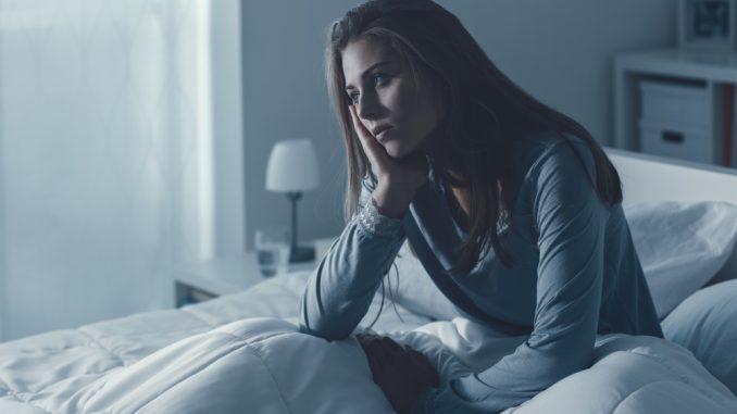Ein junges Mädchen sitzt im Bett und kann nicht einschlafen.