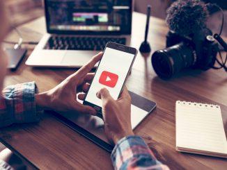 Jemand hält ein Handy in der Hand auf dem ein Youtube-Symbol zu sehen ist