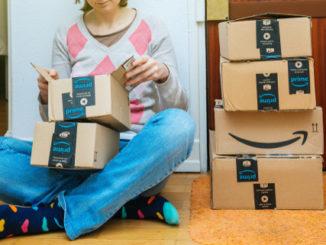 Ein junges Mädchen sitzt auf dem Boden. Um sie herum stehen Amazon Prime Pakete