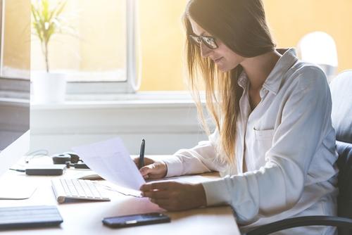 Eine jugne Frau sitzt am PC und schreibt einen Bewerbungstext. Sie aktualisiert ihre Bewerbung.